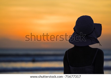 beautiful young woman standing on beach, watching sunset,