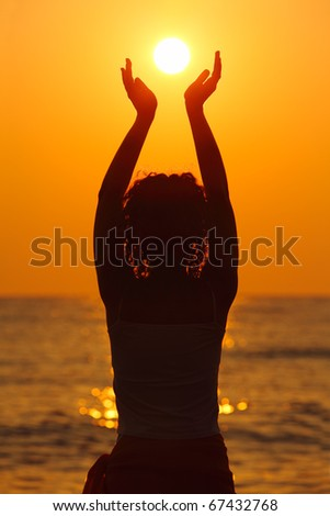 beautiful young woman standing on beach, watching sunset, holding  sun in hands