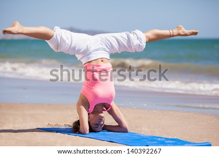 Beautiful young woman standing on her head with her legs spread as part of a yoga pose at the beach