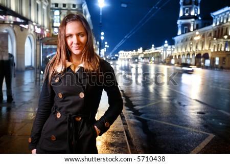 Beautiful young woman standing on illuminated street at night.