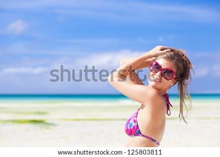 Beautiful young woman standing on the beach enjoying the sun #125803811