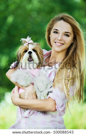 beautiful young woman standing summer park holds dog her arms