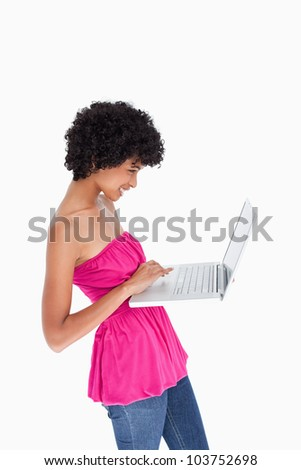 Beautiful young woman standing upright while holding a laptop