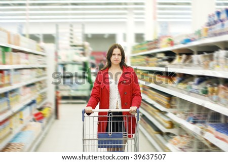 Beautiful young woman standing with a trolley at a supermarket