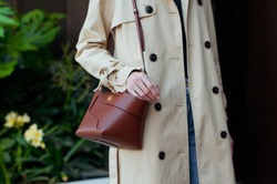Beautiful young woman staying outdoor. She is wearing beige trench coat, jeans and dark sweater. She is holding trendy leather brown handbag. Street style.