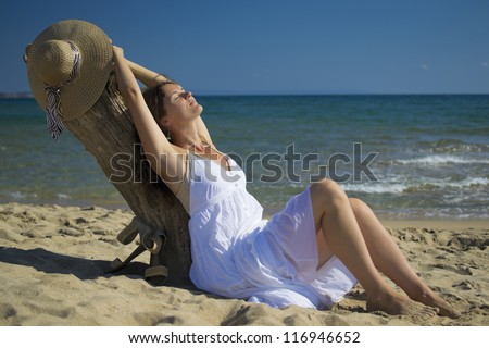 Beautiful young woman stretches whilst leaning on some driftwood on the beach