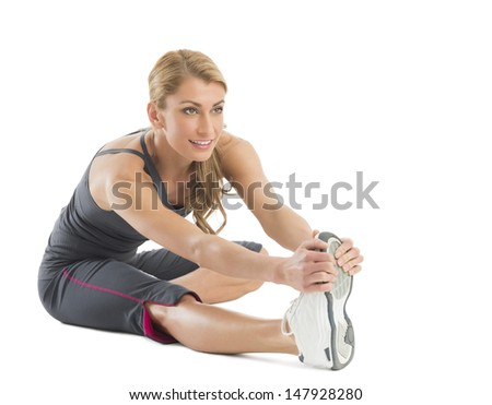 Beautiful young woman stretching to touch her toes isolated against white background
