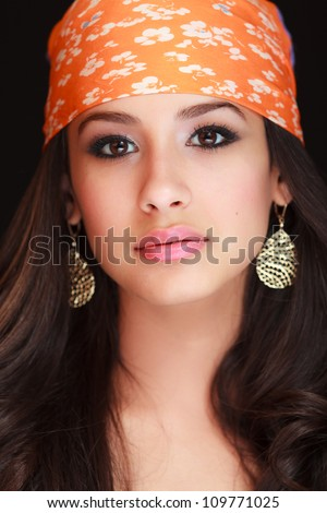 Beautiful young woman studio portrait wearing a colorful bandana on a black background.