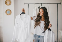 Beautiful young woman stylist standing near rack with hangers with white clothes. Shopaholic with many clothes on white background.