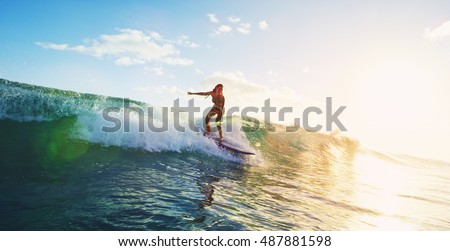 Beautiful young woman surfing at sunset #487881598