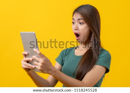 Beautiful young woman surprised facial expression after seeing shocking, amaze deal in mobile phone isolated on yellow background. Studio shot.