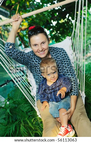 Beautiful young woman swings on a hammock with a young son in their garden