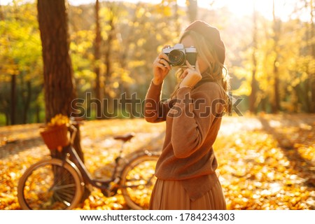 Beautiful young woman takes photos with a retro camera in autumn forest. Smiling girl enjoying autumn weather. Rest, relaxation, lifestyle concept.