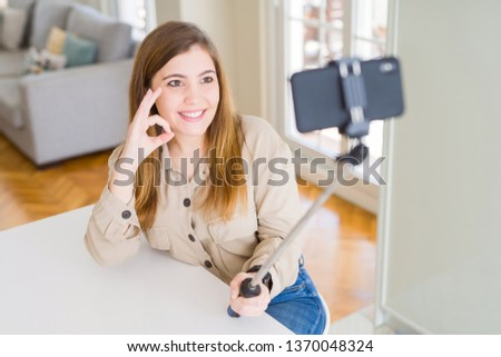Beautiful young woman taking a picture using selfie stick doing ok sign with fingers, excellent symbol
