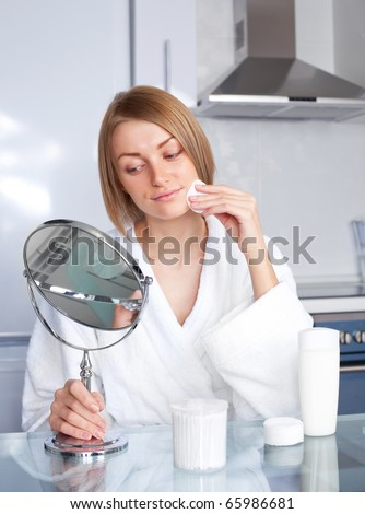 beautiful young woman taking care of her face at home