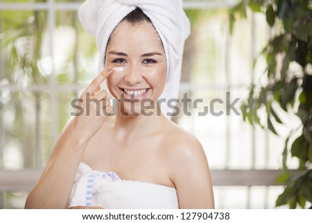 Beautiful young woman taking care of her skin