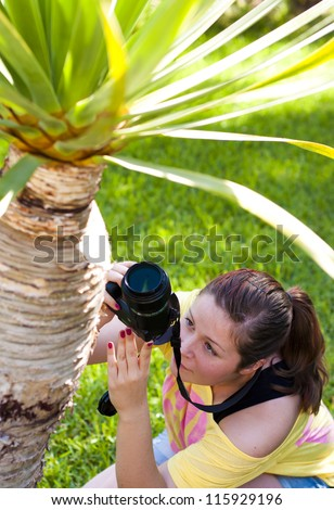 Beautiful young woman taking photos of a palm tree outdoors