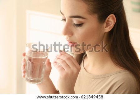 Beautiful young woman taking pill at home Stockfoto ©