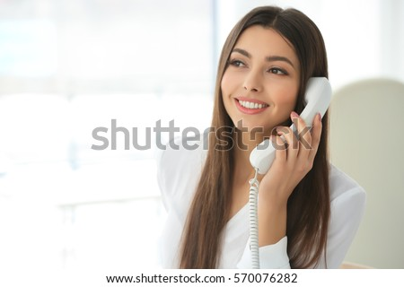 Beautiful young woman talking by telephone in office #570076282