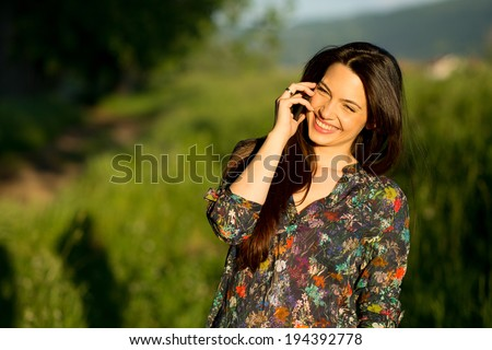 Beautiful young woman talking on the phone laughing