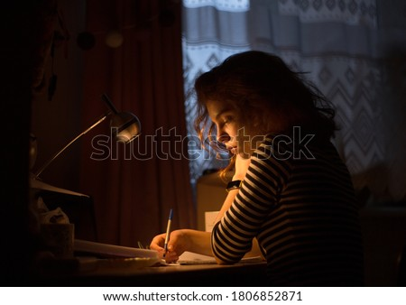 beautiful young woman, teenage girl, student, schoolgirl sits at a desk in a dark room under the light of a table lamp. She writes in a notebook, thinks, prepares with concentration for the exam Foto stock ©