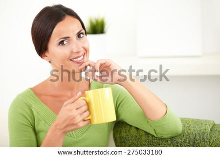 Beautiful young woman toothy smiling at the camera while touching her chin and holding a yellow mug