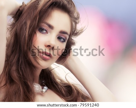 Beautiful young woman touching her hair on colorful background