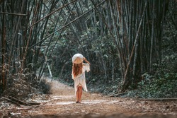 beautiful young woman tourist in hat at bamboo forest