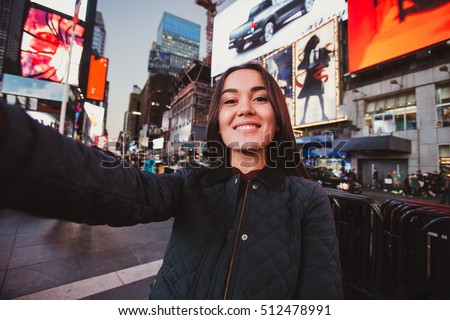 Beautiful young woman tourist taking selfie portrait New York City, Manhattan, Times Square. Multiethnic asian caucasian woman makes photo for her travel blog.