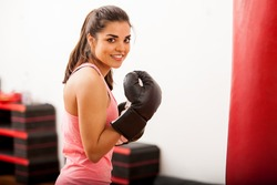 Beautiful young woman training next to a punching bag and wearing boxing gloves