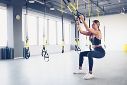 Beautiful young woman training with suspension trainer sling or suspension straps in gym. Upper body exercise concept on TRX.