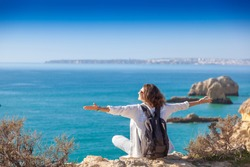 Beautiful young woman traveler on the rocks on the Atlantic coast, the Algarve, Portugal, a popular destination for travel in Europe