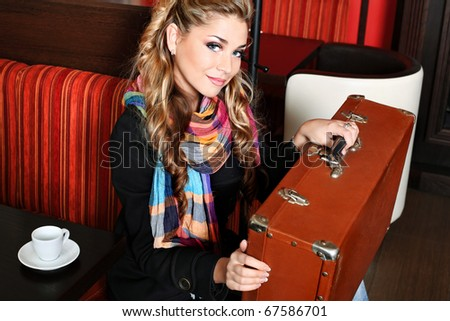Beautiful young woman traveller with an old suitcase at a caf