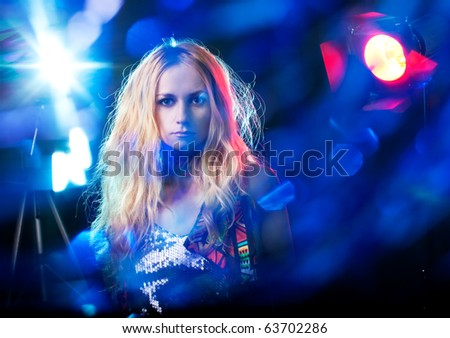 Beautiful young woman under the light flashes