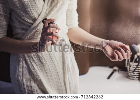 Beautiful young woman uses bottle of perfume at home, closeup