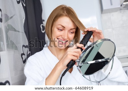 beautiful young woman using a hair straightener at home
