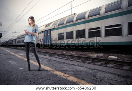 Beautiful young woman using a mobile phone on the platform of a train station