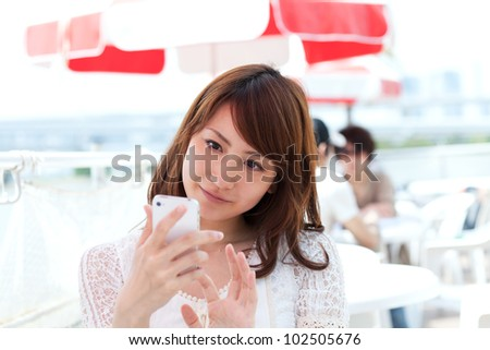 Beautiful young woman using a mobile phone. Portrait of asian