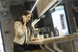 Beautiful young woman using cell phone while sitting at bar counter