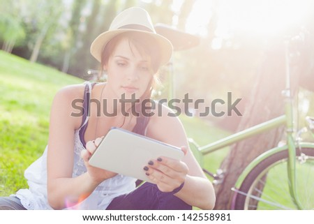 Beautiful young woman using digital tablet sitting next to her bike
