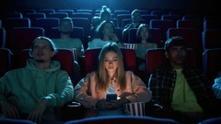 Beautiful young woman using her phone for texting while watching a movie at the cinema. Technology, entertainment concept. Front view. Web Banner