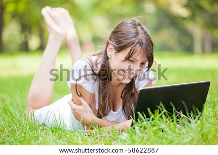 Beautiful young woman using laptop at outdoor