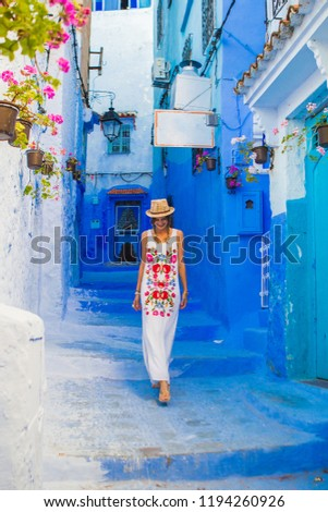 beautiful young woman visiting and enjoying the blue street of moroccan city, traveler girl