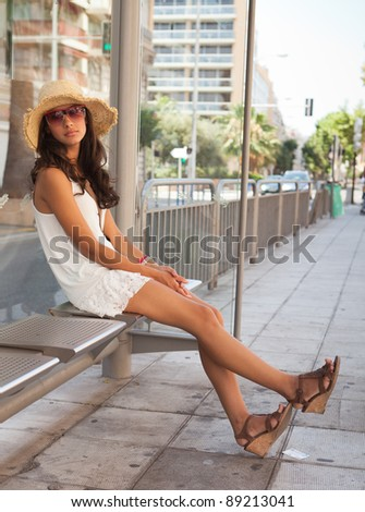 Beautiful young woman waiting for a bus in the French Riviera in Nice, France.