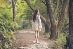 Beautiful young woman walking in park