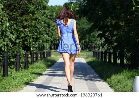 Beautiful young woman walking in summer park