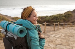 Beautiful young woman walking on a path alonside the coastline - Sportive woman carrying a yoga mat on top of her backpack, on a hike on the mountain