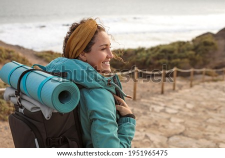 Beautiful young woman walking on a path alonside the coastline - Sportive woman carrying a yoga mat on top of her backpack, on a hike on the mountain Stock photo ©