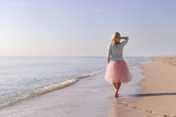 Beautiful young woman walking on the sandy ocean beach. Summer sea vacations. Smiling girl on the beach. Happy woman enjoying vacation.