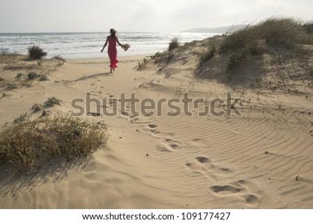 Beautiful young woman walking through the sand dunes towards  beach